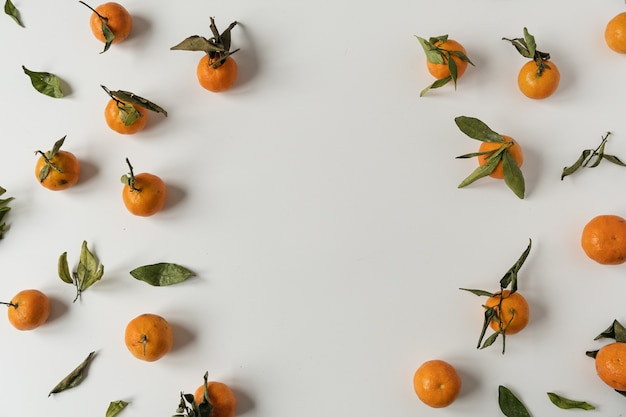 Moldura redonda com espaço de cópia em branco feito de laranjas cruas, frutos de tangerina com padrão de folhas verdes em branco