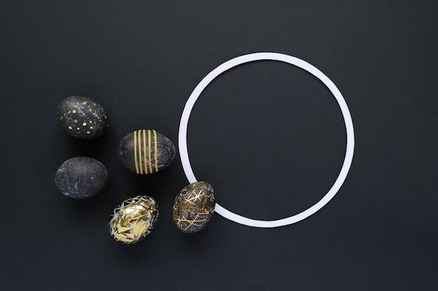 Moldura redonda com ovos de páscoa pretos com padrão ouro sobre fundo preto. páscoa luxuosa