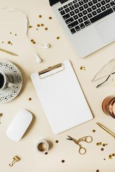 Moldura redonda da área de trabalho da mesa do escritório em casa com laptop, espaço de cópia em branco simulado para área de transferência, fones de ouvido, café, papelaria em bege