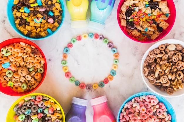 Moldura redonda de cereais com tigelas e garrafas