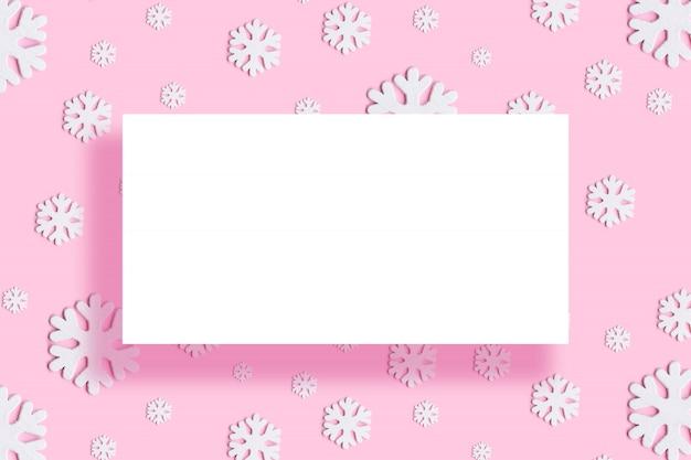 Moldura redonda de natal feita de flocos de neve de férias decoração branca em fundo rosa
