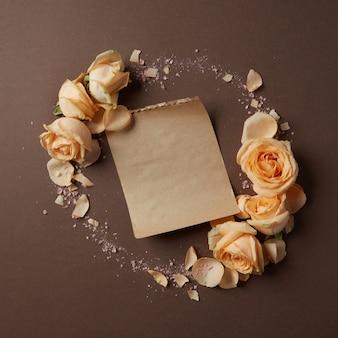 Moldura redonda de rosas em um fundo marrom com um pedaço de papel para o seu texto, disposição plana