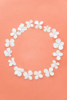 Moldura redonda feita de flores brancas frescas sobre fundo rosa pastel