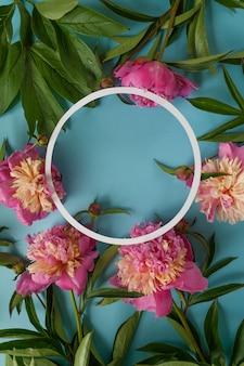 Moldura redonda. peônias rosa sobre fundo azul