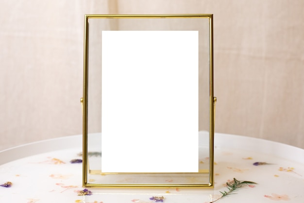 Moldura retrô de ouro ou bronze com arranhões envelhecidos para fotos, textos, imagens ou pinturas na vista lateral da mesa branca