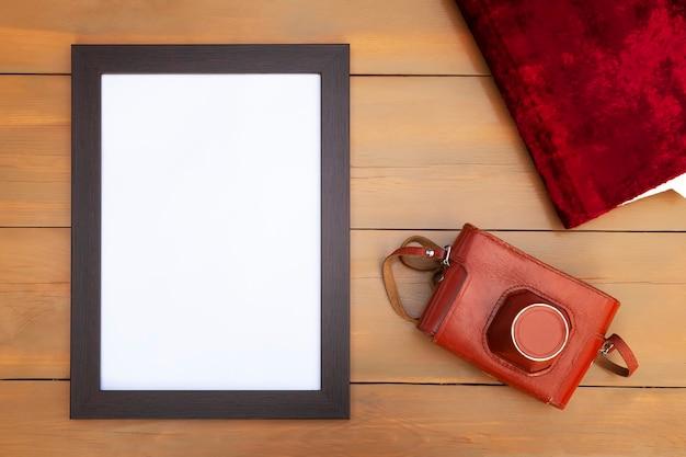 Moldura vazia com câmera retro e álbum de fotos em uma mesa de madeira.