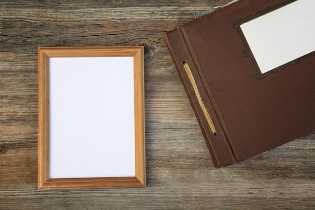 Moldura vazia e álbum de fotos antigo em uma mesa de madeira.