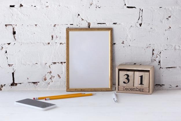 Moldura vazia em branco ou folha na parede de tijolo branco com smartphone e lápis. copyspace. 31 de dezembro, resoluções de ano novo.
