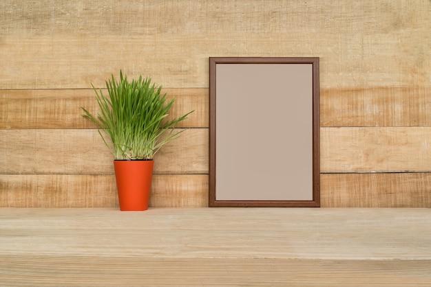 Moldura vazia em uma parede de madeira. planta de casa verde em cima da mesa.