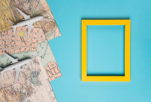 Moldura vazia, mapas e avião de brinquedo