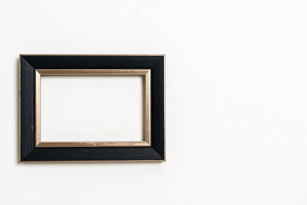 Moldura vazia no fundo da parede branca com espaço de cópia