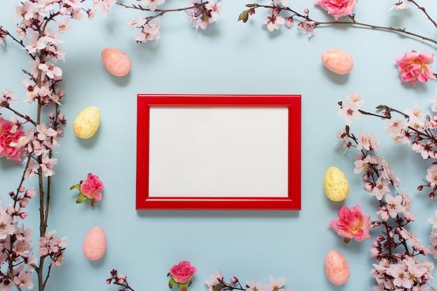 Moldura vermelha em branco com flores e ovos de páscoa