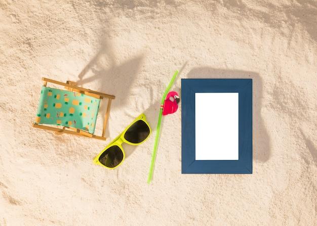 Moldura vertical azul e óculos de sol na praia
