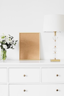 Moldura vertical dourada e buquê de flores frescas em móveis brancos, decoração de casa de luxo e design f ...