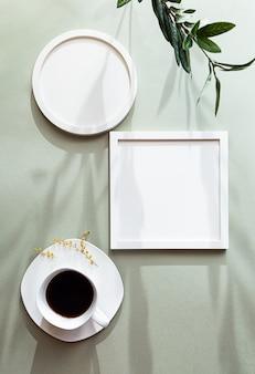 Molduras brancas redondas e quadradas em branco e uma xícara de café preto branco