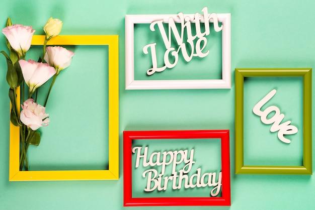 Molduras coloridas para fotos ou imagens com flores e letras sobre uma superfície verde.