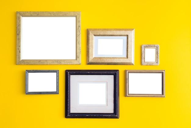 Molduras de madeira vazias em branco na parede amarela.