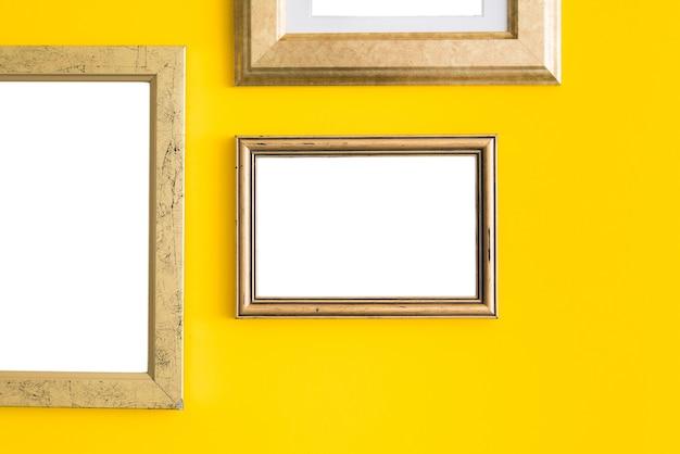 Molduras de madeira vazias em branco na superfície amarela.