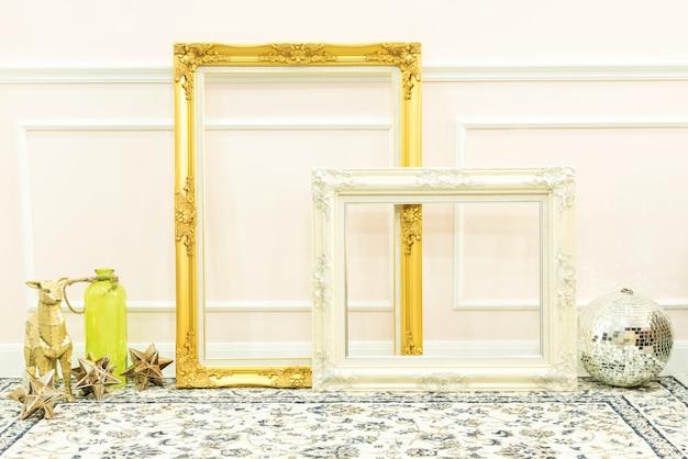 Molduras de madeira vintage douradas e brancas em branco e coisas decorativas no chão