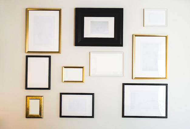Molduras e molduras vazias de ouro e preto na parede branca simulados para suas fotos ou cópia de texto