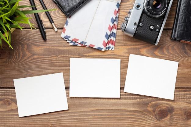 Molduras em branco, câmera e suprimentos na mesa de madeira. vista do topo.