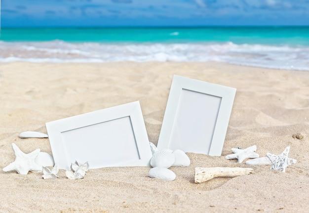 Molduras em branco na praia de areia com conchas, estrelas do mar e velas.