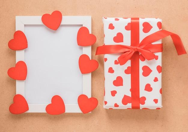 Molduras para fotos com corações de ornamento perto da caixa de presente