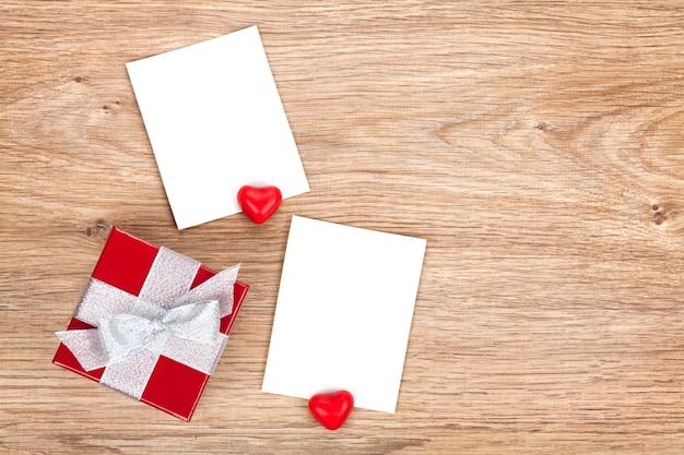 Molduras para fotos de dia dos namorados em branco e pequena caixa de presente vermelha com fundo de madeira