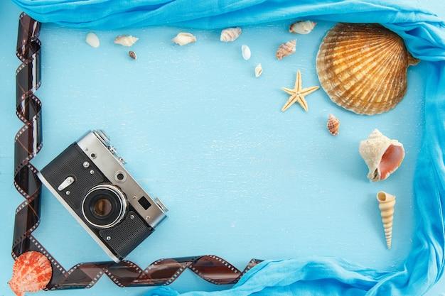 Molduras para fotos de papel em branco com estrelas do mar, conchas e itens na mesa de madeira.
