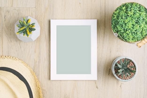 Molduras para fotos em branco colocado sobre um piso de madeira, adornada com vasos de plantas e chapéus