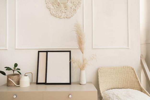 Molduras para fotos em branco com espaço de cópia na mesa. juncos fofos, buquê de grama dos pampas, planta doméstica, cadeira de vime contra parede branca