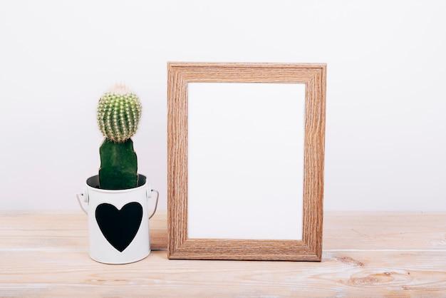 Molduras para fotos em branco e planta suculenta com heartshape no pote sobre a mesa de madeira