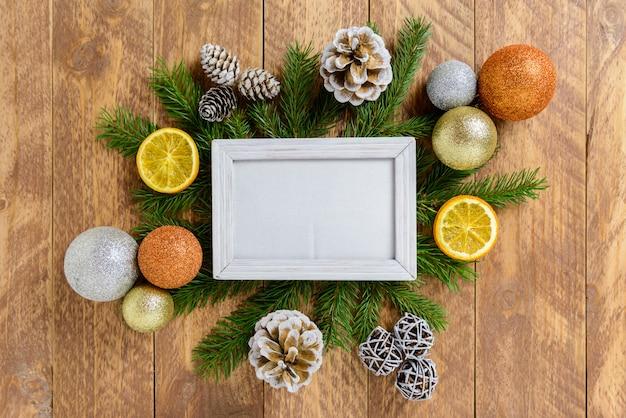 Molduras para fotos entre a decoração de natal, com bolas coloridas e pinhas em uma mesa de madeira marrom. vista superior, moldura para copiar o espaço.