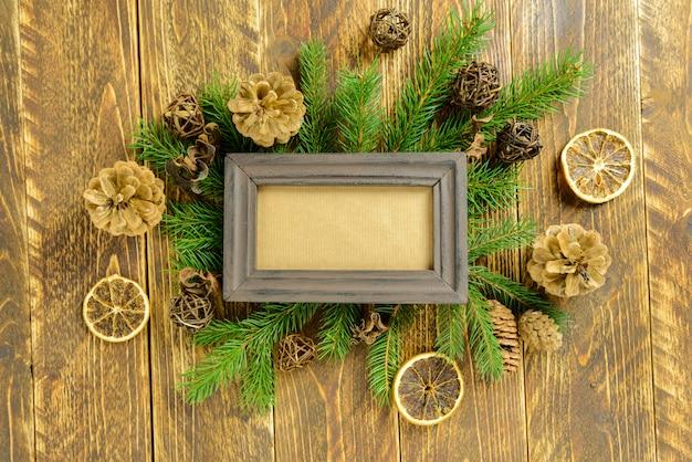 Molduras para fotos entre a decoração de natal, com pinhas em uma mesa de madeira marrom. vista superior, moldura para copiar o espaço.