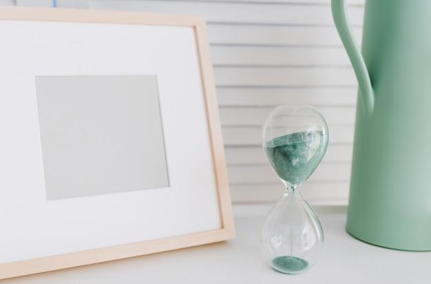 Molduras para fotos vazias, pote de rega e uma ampulheta ou relógio de areia