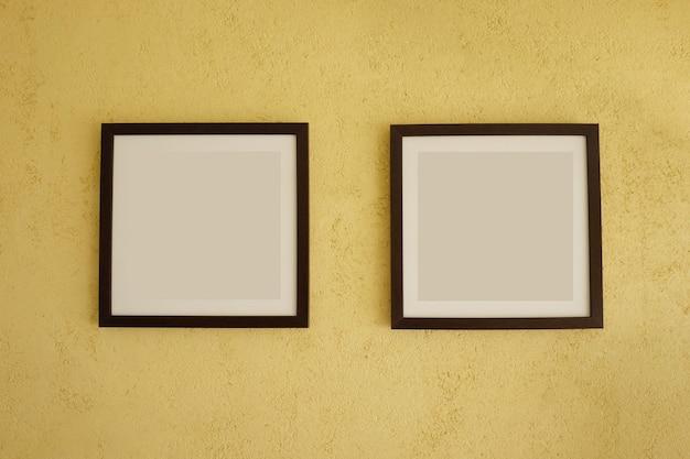 Molduras vazias em paredes amarelas vintage.
