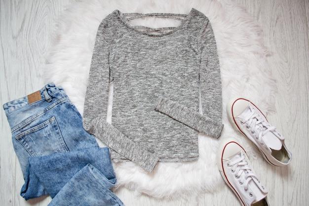 Moletom cinza, tênis branco e calça jeans.