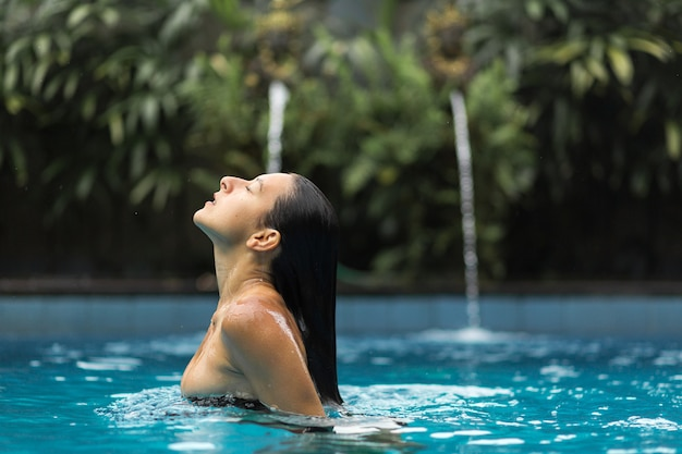 Molhado blackhair mulher sexy maiô posando na piscina.