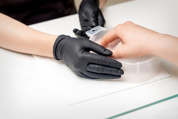 Molhar as unhas na banheira com água em mesa branca sob supervisão de uma manicure