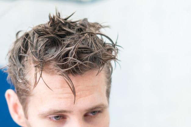 Molhar o cabelo de homem e segurar uma toalha depois de tomar banho em casa