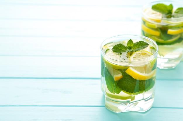 Molhe a desintoxicação com limão, limão e hortelã em um fundo azul. bebida de desintoxicação com espaço de cópia