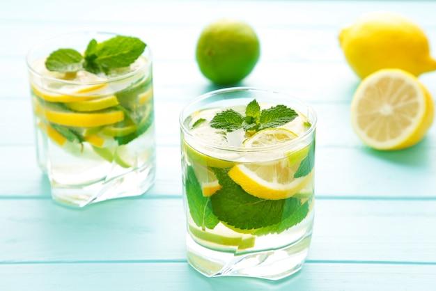 Molhe a desintoxicação com limão, limão e hortelã em um fundo azul.