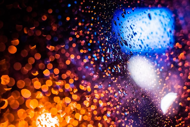 Molhe a janela com o fundo da cidade à noite de outono. desfocar. luzes brilhantes, bokeh.