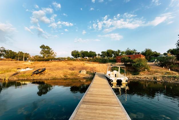 Molhe de madeira com barco ancorado e reflexões na água do lago
