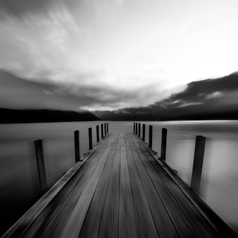 Molhe do barco e um lago calmo no nascer do sol, nova zelândia.