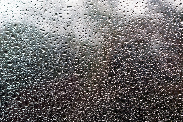 Molhe gotas no vidro contra o céu e as árvores.