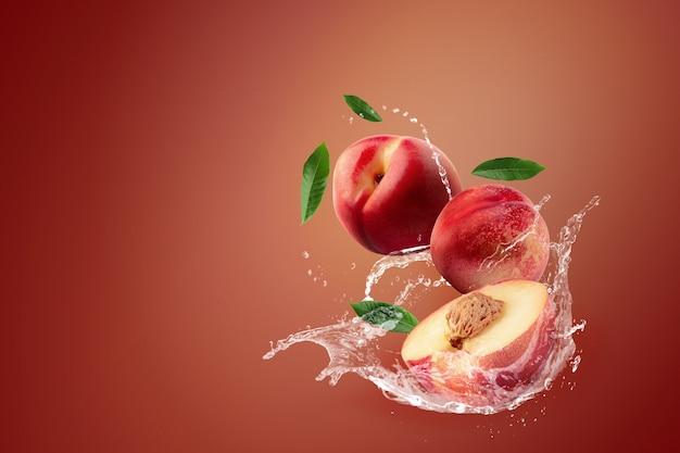 Molhe o espirro no fruto fresco da nectarina no fundo vermelho.