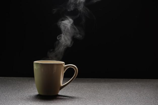 Molhe quente na tabela de madeira, beba o vapor e copie o espaço, foco seletivo. conceito quente de bebidas