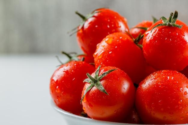 Molhe tomates suculentos em um prato branco sobre uma superfície branca e suja. vista lateral.