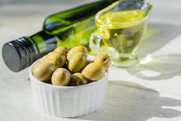 Molheira de vidro com azeite de oliva extra virgem, azeitonas verdes frescas e garrafa na mesa de madeira.